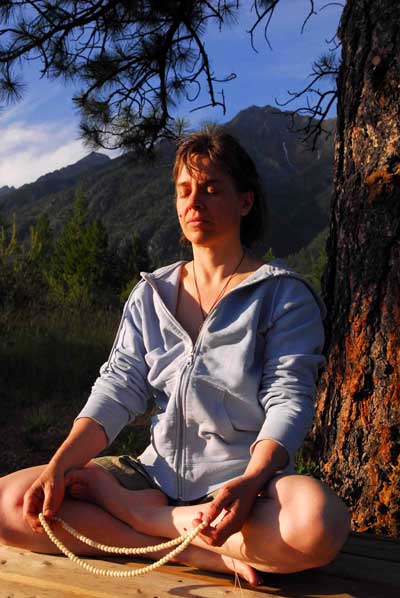woman meditating by mountain