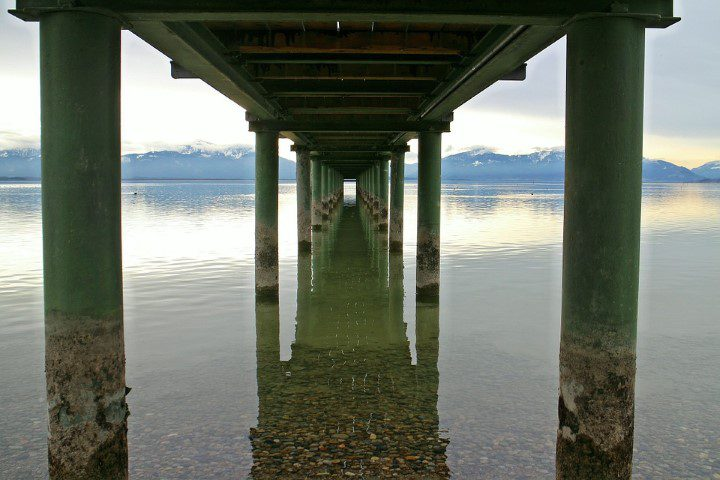underneath view of pier on a lake with mountains in background