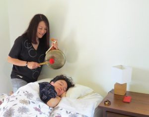 Gong waking a woman up in bed