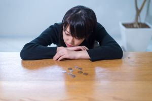 Woman slumped over desk with few coins on it