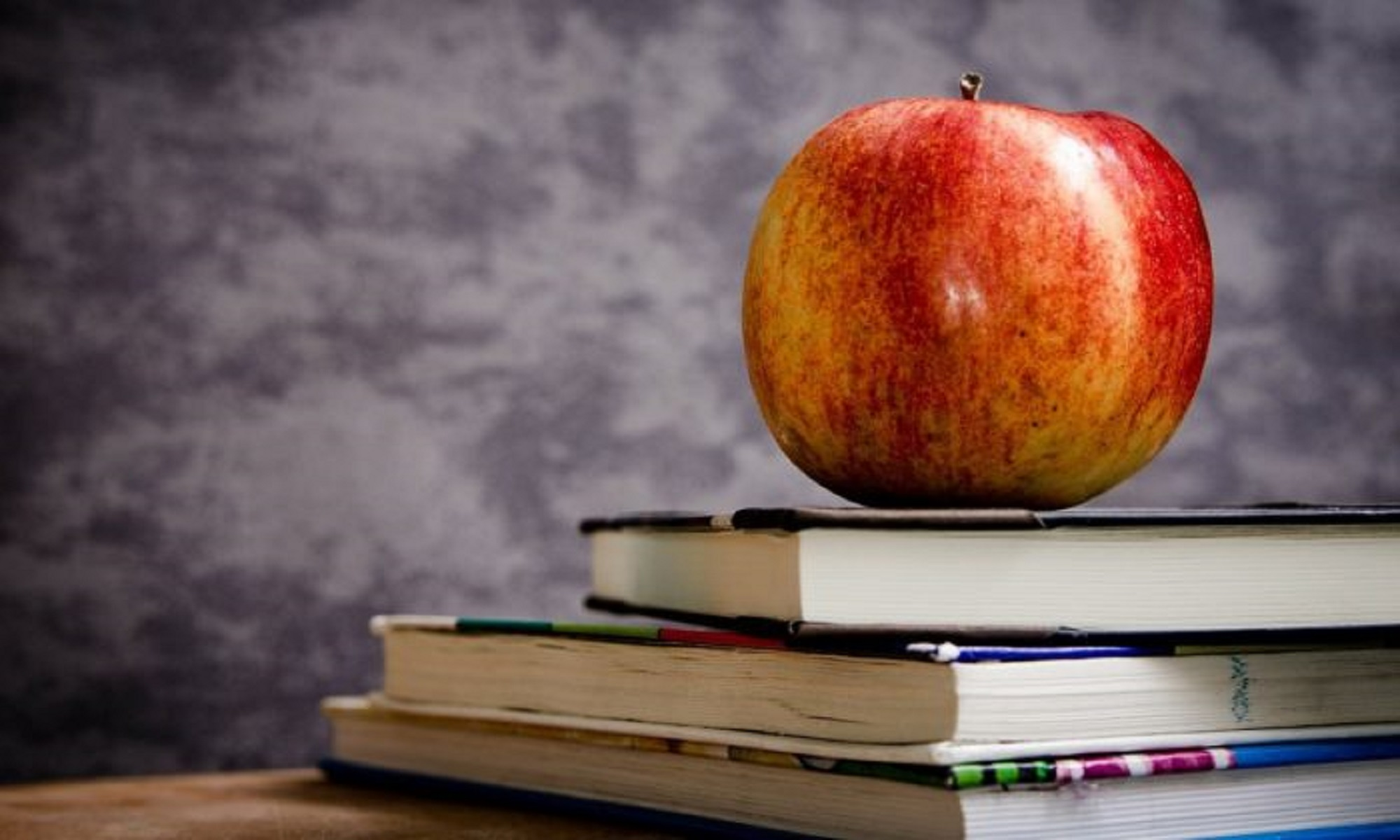 A photo of an apple on top of some books