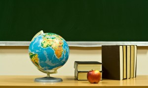 A picture of a globe, apple and some books on a desk