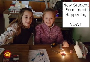 an image of two girls participating in a stem activity about electric circuits