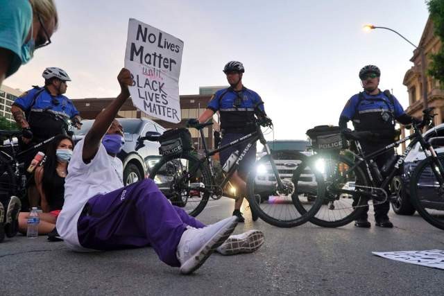 Donnell Ballard blocks traffic during a march in downtown Fort Worth, Texas on Friday, May 29, 2020. The protest was to show solidarity in the midst of the latest killing of George Floyd, an African American man by police in Minnesota. (Lawrence Jenkins/The Dallas Morning News via AP)