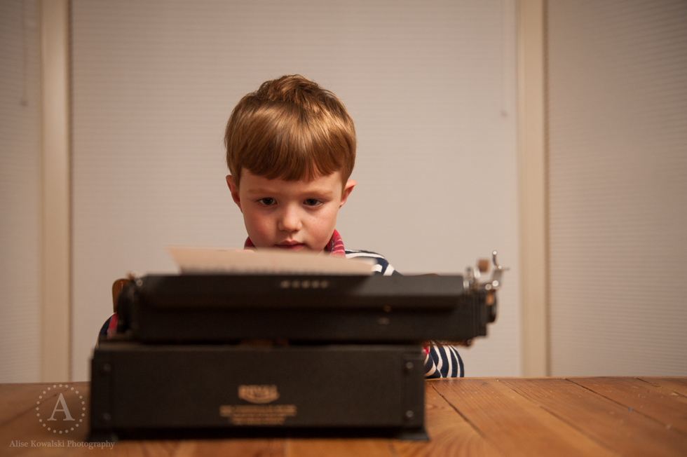 A boy, a Mississauga freelance writer, works on a white paper while using a typewriter.