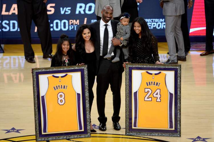 Kobe Bryant poses with his family at halftime after both his No. 8 and No. 24 Los Angeles Lakers jerseys are retired at Staples Center on Dec. 18, 2017.