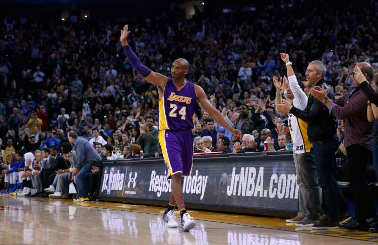 Kobe Bryant waves to the crowd after he's taken out of the game in the fourth quarter against the Golden State Warriors at Oracle Arena in January 2016.