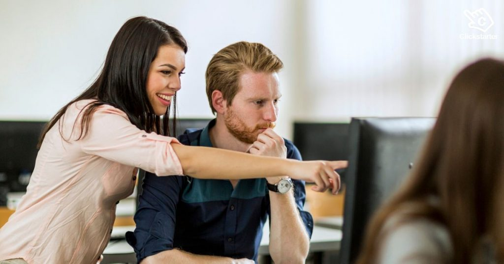 Woman showing man something on his computer screen