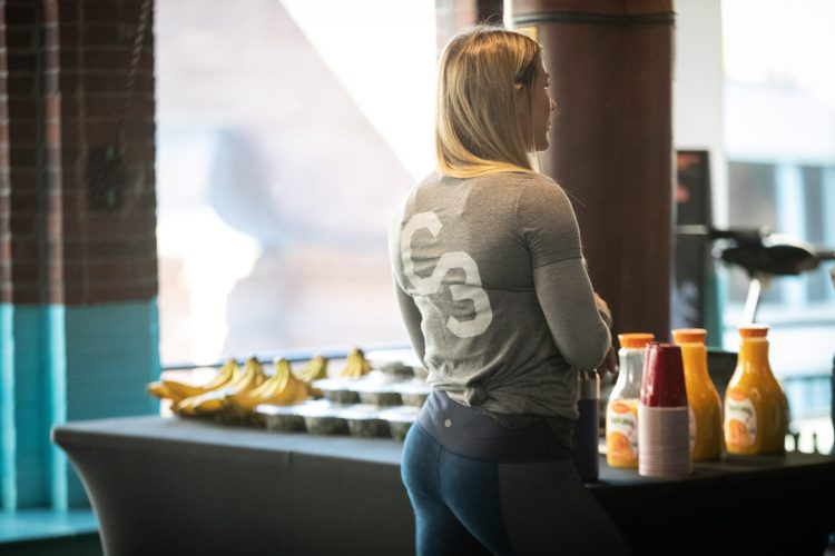 The trainer is stood in front of a table with nutritive meals, fruits and drinks.