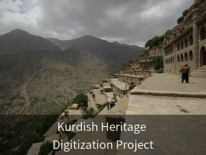 Modal box: Kurdish Heritage Digitization Project. Background image: Building in Eastern Kurdistan on mountain with man in front.