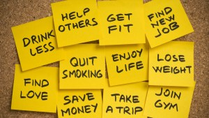 List of New Years Resolutions on yellow sticky notes on a pinboard