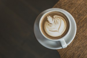 image on a latte with latte art on wooden table stop for coffee before brightonSEO