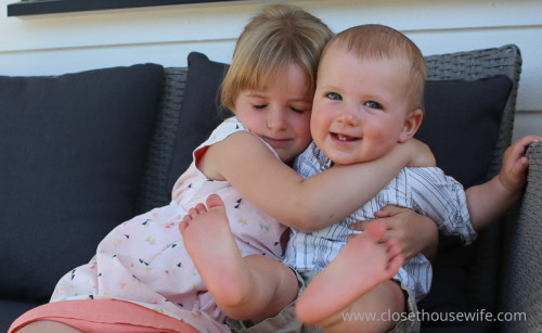 Birthday girl gives her little brother a hug