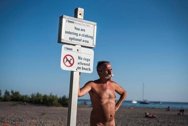 Man at clothing optional beach sign