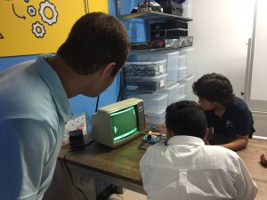 Two West Valley Boys and Girls Club members play the Pong video game while an adult looks on during the unveiling of B-STEM's Tech Innovation Village there.