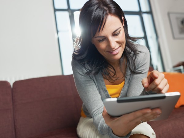mid adult woman sitting on sofa with tablet pc. Horizontal shape, front view, copy space
