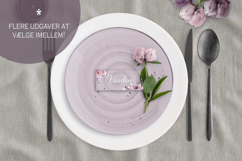 Akryl bordkort med røde og pink blomster på dækket bord med tallerken.