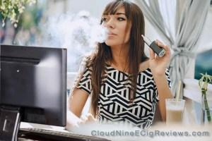 Woman vaping at computer - CloudNineEcigReviews