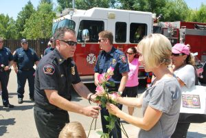 Photo by Valerie Shelton Clovis Fire Chief Michael Despain gives Karyn a pink rose.