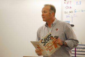 """Photo by Valerie Shelton Fresno State Football Head Coach Tim DeRuyter reads """"Hooray for Diffendoofer Day!"""" by Dr. Seuss to students in Mr. Murphy's fifth grade class."""