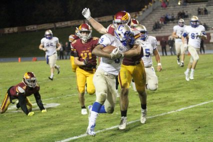 Clovis running back Samir Allen is tackled by Clovis West linebacker Dusty Schramm. Allen ran for 320 yards and four touchdowns in the Cougars loss. [Photo by Stan Miyake]