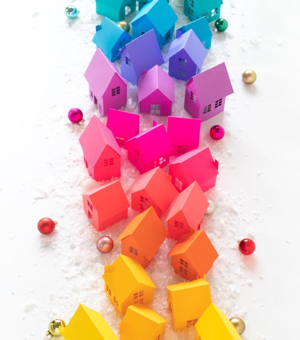 Rainbow Holiday Village with Paper + Free Templates for Cricut or Silhouette! // Decorate for Christmas with these paper houses made with vibrant Astrobrights cardstock! Turn the holiday village into a rainbow surrounded by fake snow, bottlebrush trees, and LED lights for a festive holiday display! #christmas #christmasdecor #diychristmas #holidayseason #holidaydecor #rainbow #papercrafts #freetemplate #freeprintable