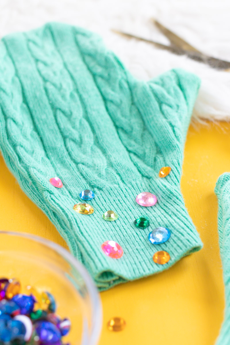 Upcycled Sweater DIY! Easy No-Sew Mittens // This easy upcycling DIY is perfect for giving new life to a thrifted sweater or old piece of clothing! Use a sweater and Aleene's Fabric Fusion to make no-sew mittens perfect for keeping warm this season. Add rhinestones for a little extra bling! #ad #nosew #diyfashion #diystyle #upcycledcrafts #bedazzled #nosewfashion #winterdiy #thrifteddiy