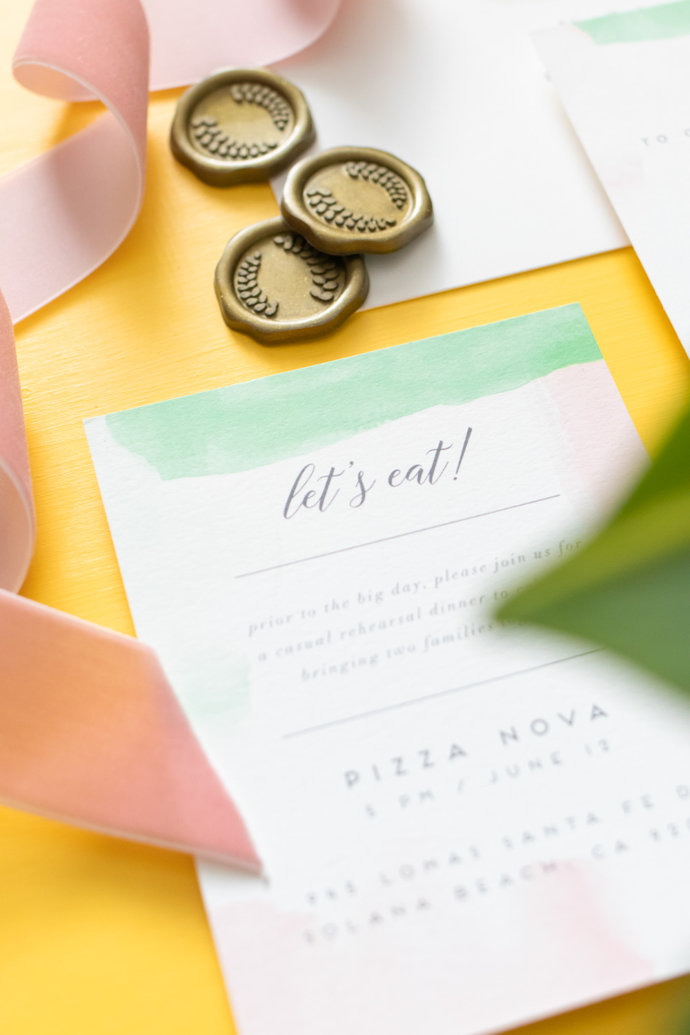 Closeup of rehearsal dinner invitations on yellow background