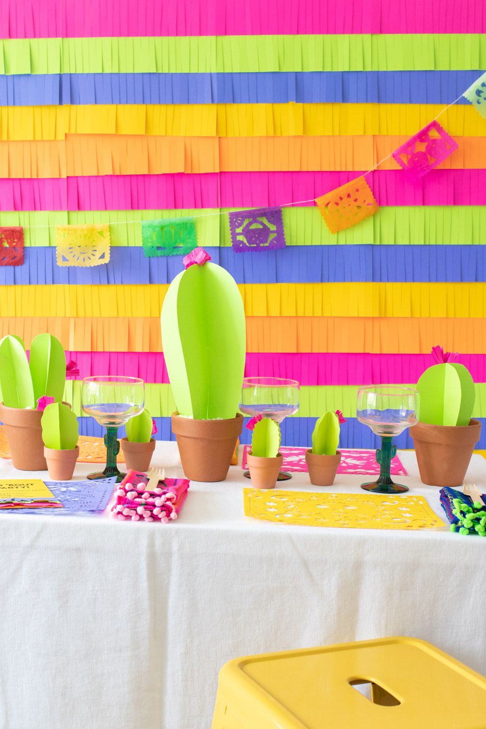 colorful paper fiesta decor table with fringe backdrop, paper cacti