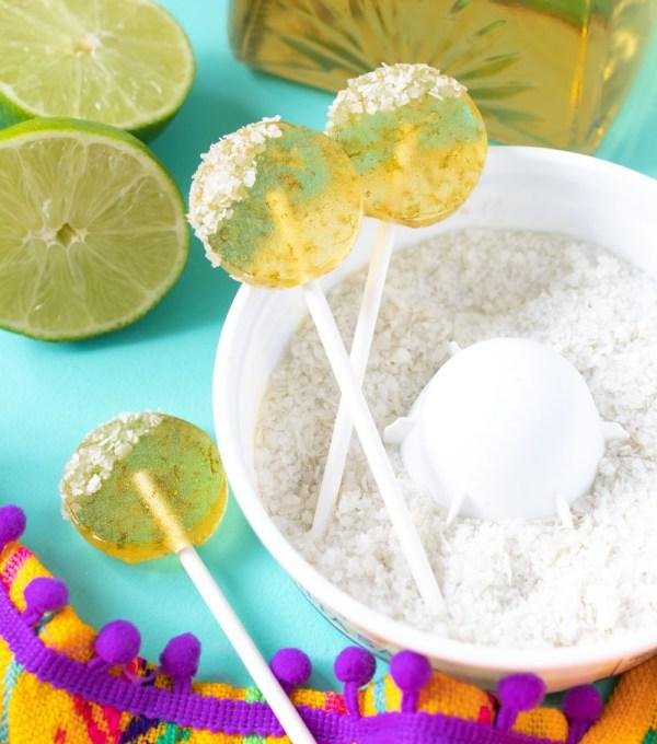 three margarita lollipops arranged in salt with bottle of tequila