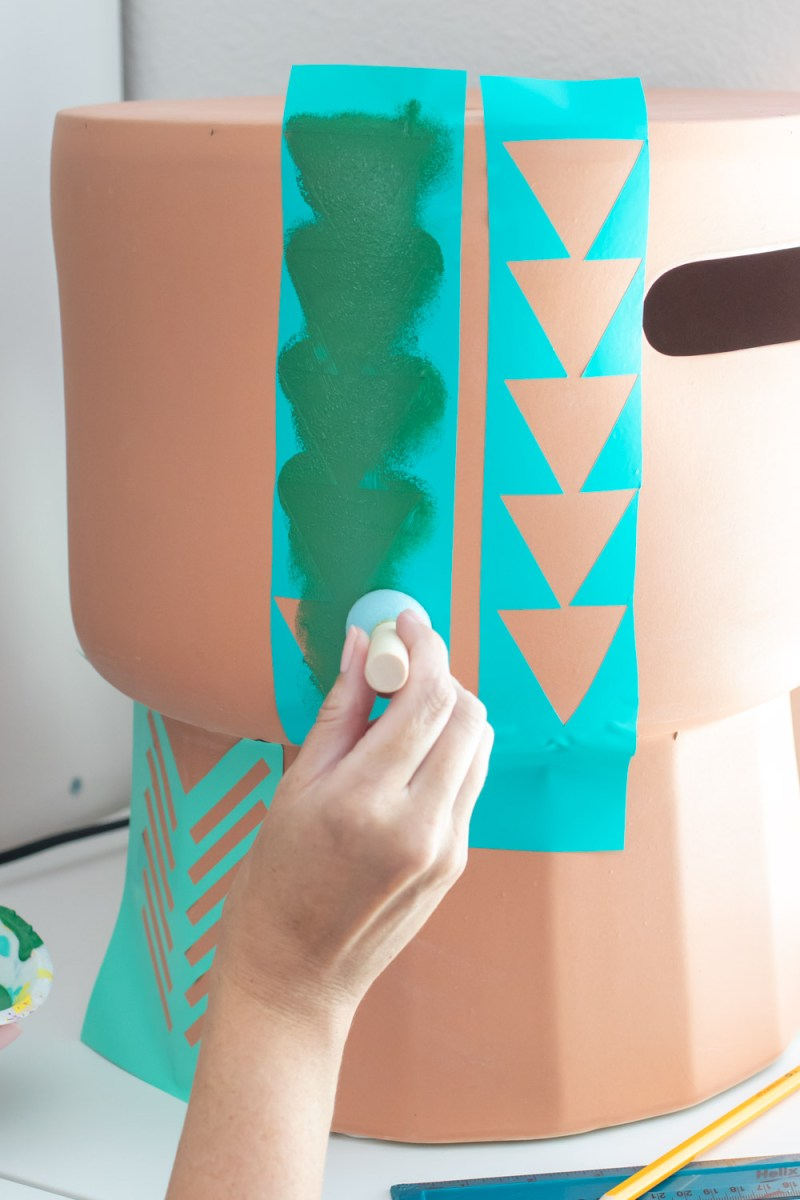 dabbing paint onto geometric vinyl stencil for making stenciled side table