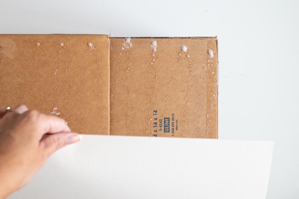 sticking poster board to cardboard box