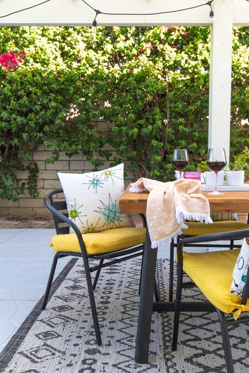 fall outdoor dining space with mid-century patterned pillows