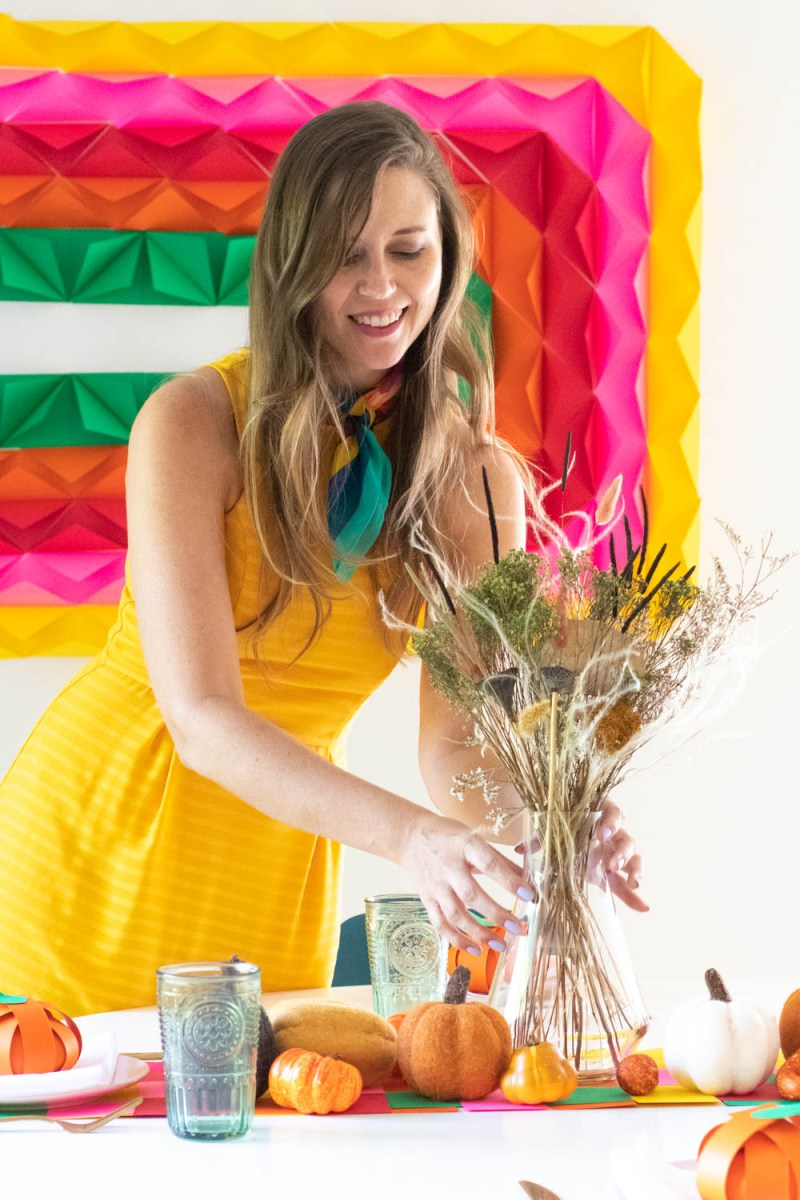 woman holds vase surrounded by DIY thanksgiving decor