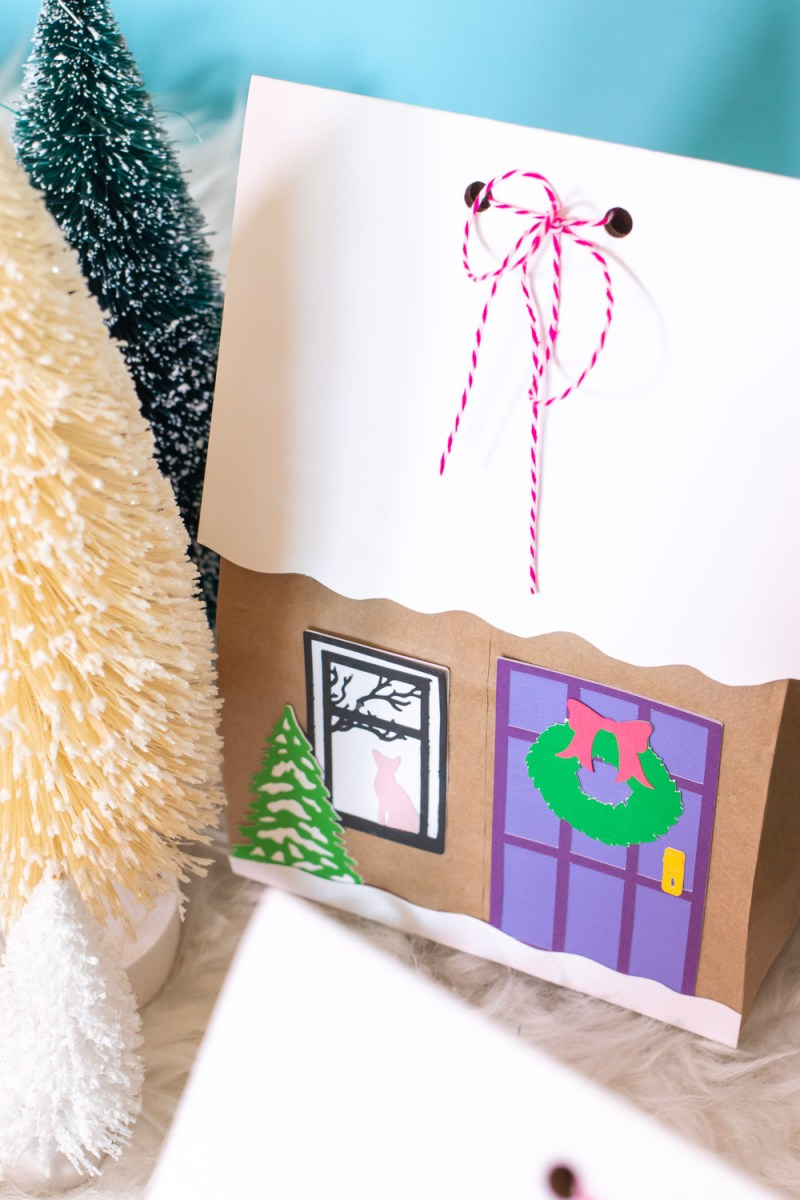 paper pieces decorate gingerbread house paper gift bags surrounded by trees