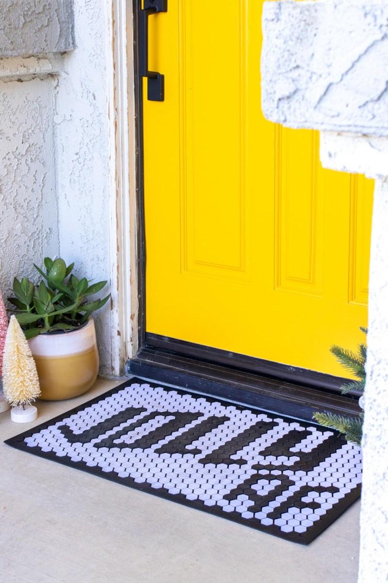 doormat and mini trees in front of bright yellow front door