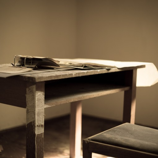 old wooden desk with scattered papers