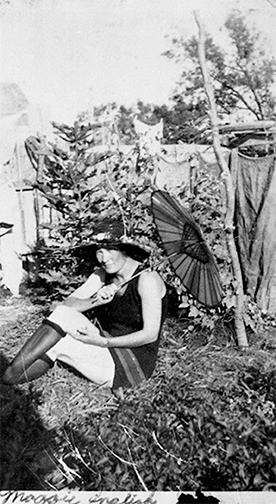 B&W photo of Maggie English sitting on ground holding an umbrella, courtesy of Byron Smith