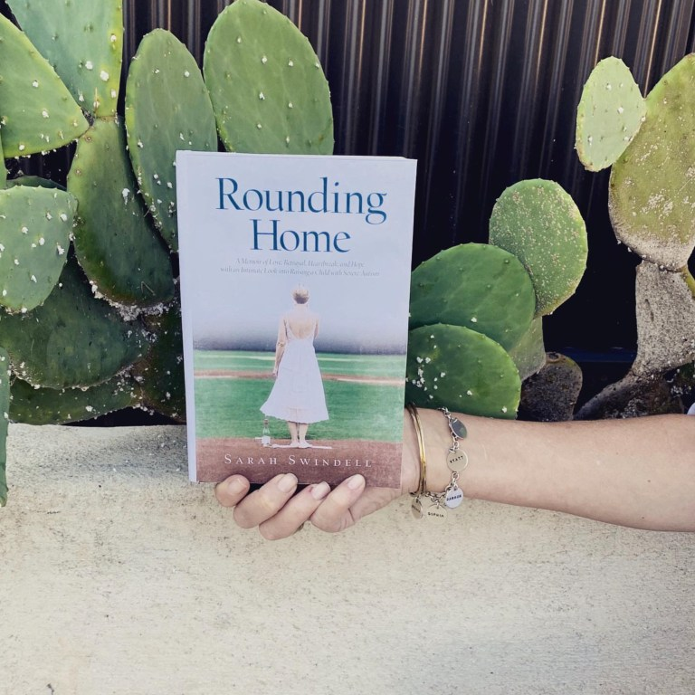 photo of woman's hand holding a hard cover edition of Rounding Home in front of a large cactus