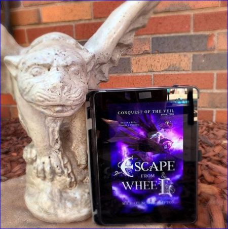 Bookstagram: photo of Escape from Wheel on black tablet, propped on a stone gargoyle, against a reddish brick wall.