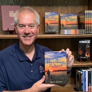 Dan V Jackson Author Photo - Dan is holding a copy of his book, Rainbow Bridge.