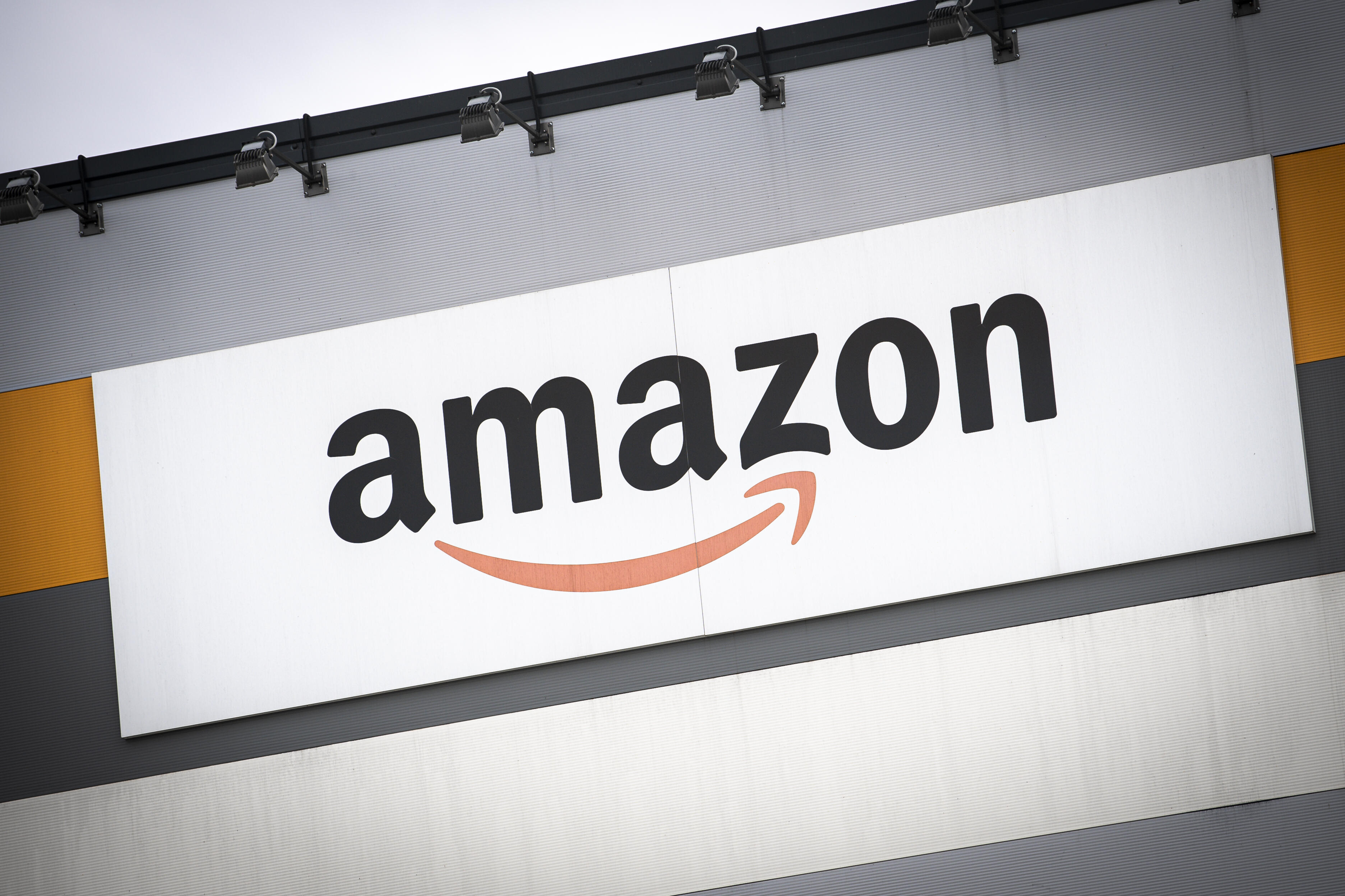 The outside of an Amazon warehouse with the company logo prominently displayed.