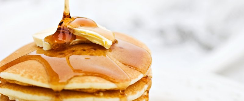 Maple syrup poured over a stack of pancakes