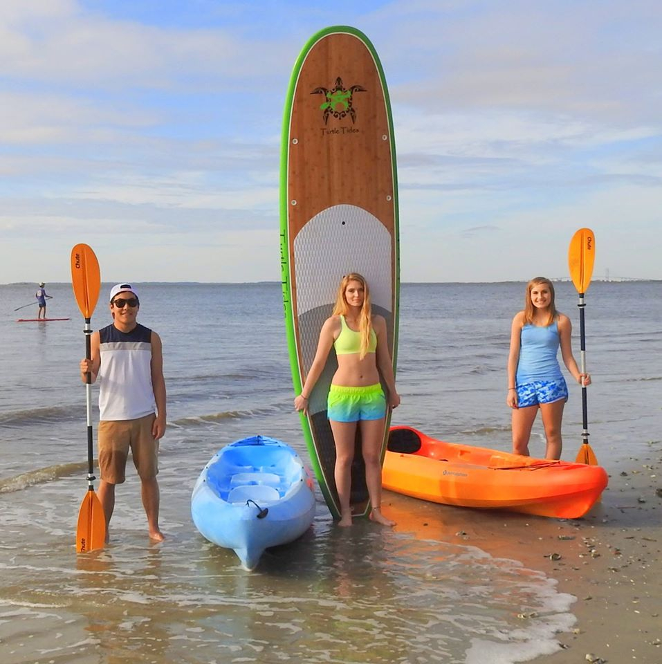 Kids displaying their Turtle Tides paddle boards and kayaks.