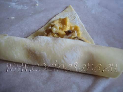 Enrolllando el croissant de la parte más ancha a la parte más delgada y sellar los bordes