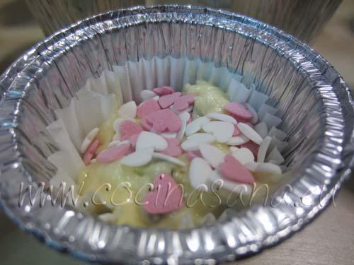 Echa encima de los muffin los corazoncitos de azúcar