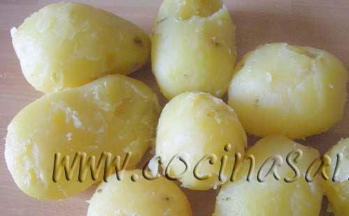 Cuece las patatas sin pelarlas ni cortarlas en una olla con agua