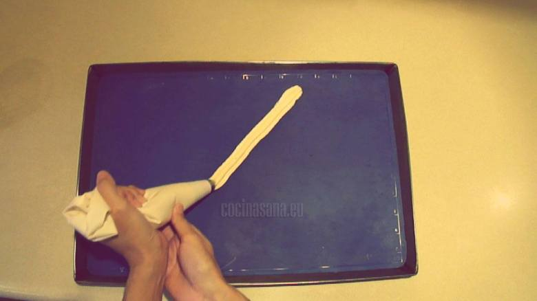Escudillar la masa en la charola con papel o tapete siliconado