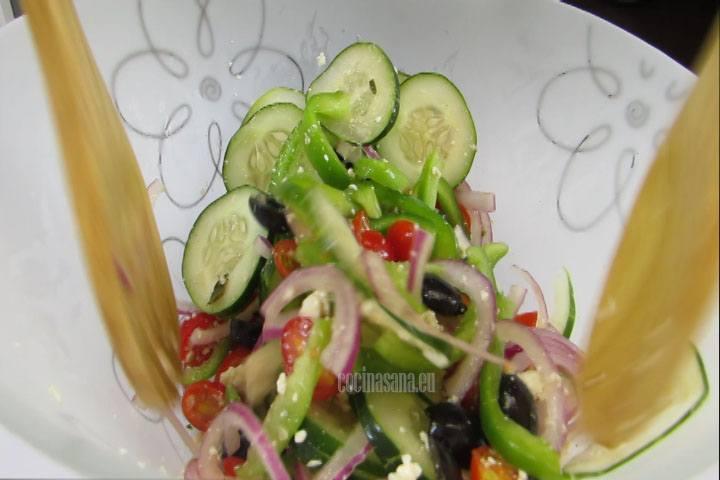 aliñar con el aceite la ensalada griega, añadir más sal y pimienta si es necesario