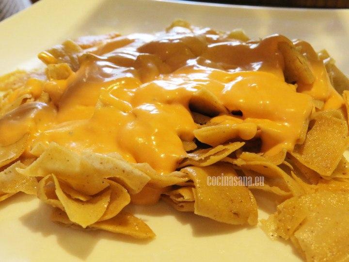 Colocar las tortillas crujientes en un recipiente o plato, agregar la salsa,